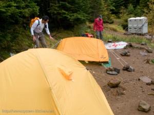 雨の中準備をする登山家客